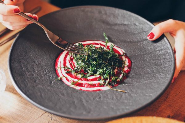 Dettaglio piatto di risotto con mani officina del riso